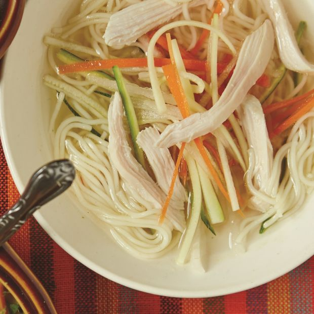 crystal clear chicken soup with julienned vegetables and angel hair